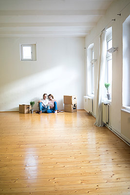 Mature couple sitting on floor in empty room next to cardboard boxes using tablet - p300m1562259 by Robijn Page