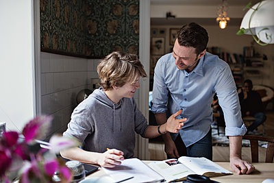 Smiling son thanking father for his help in doing homework at home - p426m2101606 by Maskot