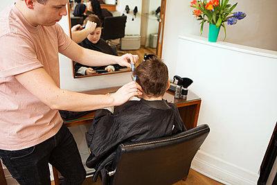 Male hairdresser trimming boy's hair in hair salon - p429m1407736 by Nancy Honey