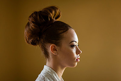 Close up portrait of a young woman with her hair in a bun,  - p429m819843 by Zave Smith