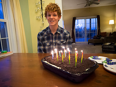 Caucasian boy smiling with birthday cake - p555m1411522 by Jeff Greenough