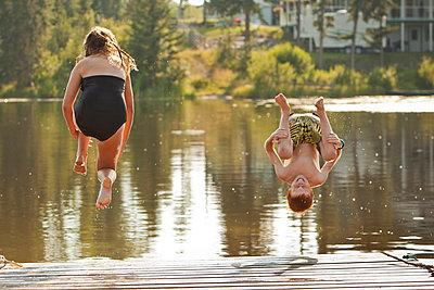 Caucasian children jumping into lake - p555m1411545 by John Lee
