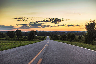 Diminishing perspective of rural road at sunset - p924m1157672 by Lena Mirisola