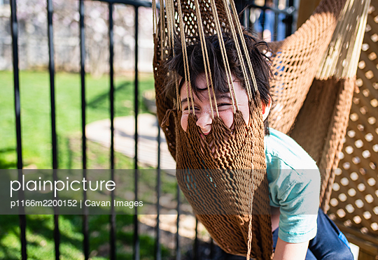 Silly boy sitting in a hammock in a backyard on a summer day. - p1166m2200152 by Cavan Images