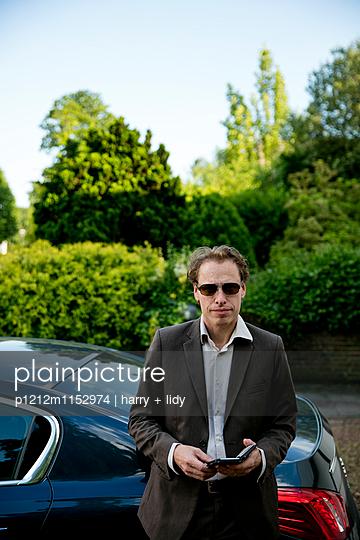 Mann am Auto mit Smartphone - p1212m1152974 von harry + lidy
