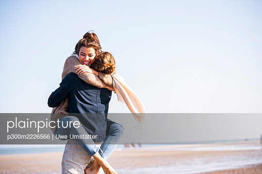 Happy young woman embracing boyfriend at beach against clear sky on sunny day - p300m2226566 by Uwe Umstätter