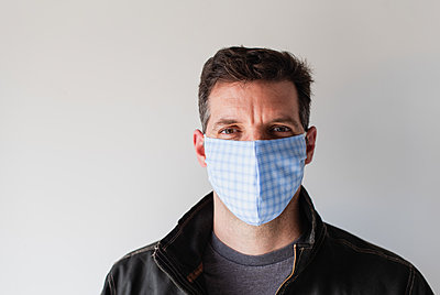 Man wearing homemade cloth face mask during Covid 19 pandemic. - p1166m2174104 by Cavan Images