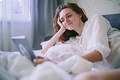 Young woman lies in bed and uses a tablet - p1363m1423673 by Valery Skurydin