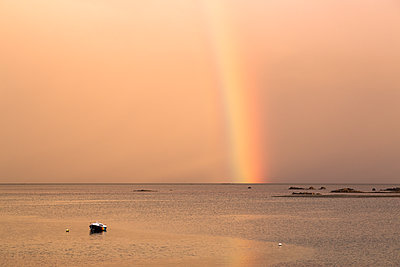 Rainbow over the sea and drawn on the boat - p1682m2264048 by Régine Heintz