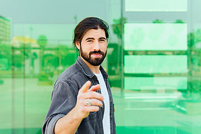 Handsome man gesturing while standing in front of green glass wall - p300m2276824 by Miguel Frias