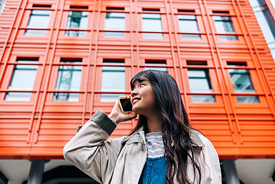 Young woman talking on mobile phone in front of building - p300m2298953 von Angel Santana Garcia