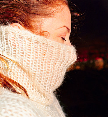woman hiding face behind sweater, side-view - p3012480f by fStop