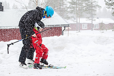 Father with child skiing together - p312m1103706f by Sara Winsnes