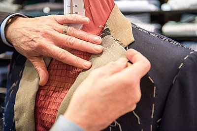 Tailor preparing bespoke suit jacket on tailors dummy, close up of hands - p429m2004132 by G. Mazzarini