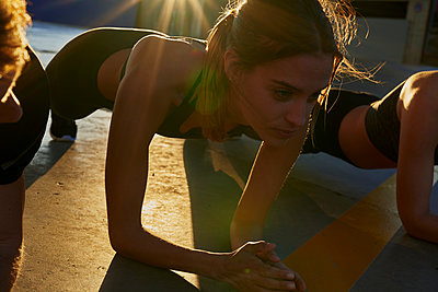 Friends doing plank in sports stadium at sunset - p429m2078588 by Pablo Calvo