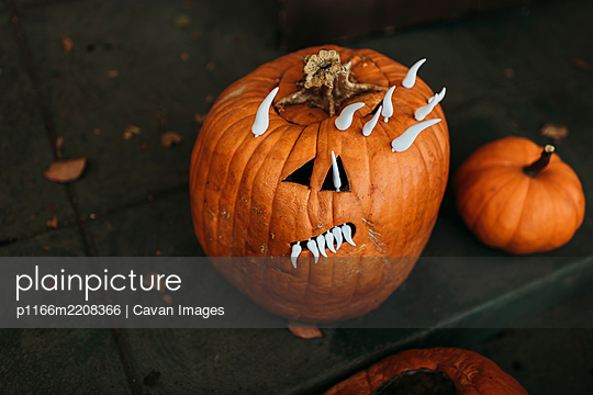 Close up of spooky carved pumpkin with teeth sitting on porch - p1166m2208366 by Cavan Images