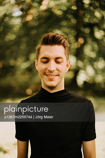 Young man in black shirt - p1267m2259744 by Jörg Meier