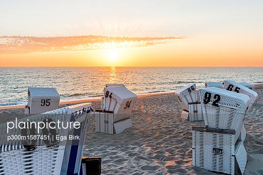 Germany, Schleswig-Holstein, Sylt, beach and empty hooded beach chairs at sunset - p300m1587451 von Ega Birk