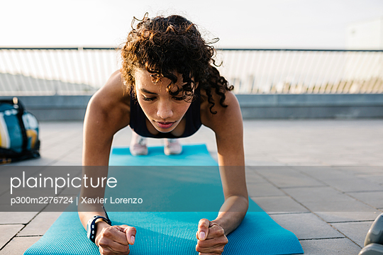 Female athlete exercising in plank position on exercise mat - p300m2276724 by Xavier Lorenzo