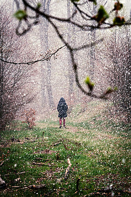 Woman walking in snow flurry - p1168m1132628 by Thomas Günther