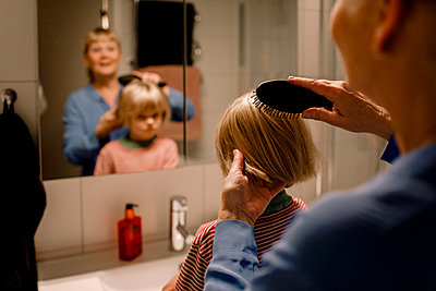 Grandmother combing hair of grandson in bathroom at home - p426m2195188 by Maskot