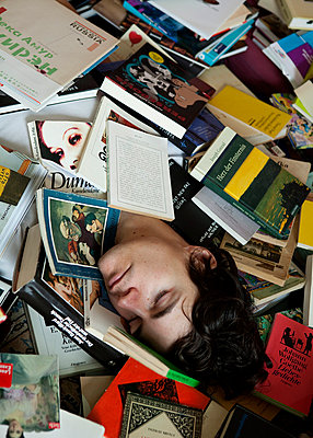 Man sleeping in between books - p7580064 by L. Ajtay