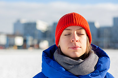Young woman with closed eyes and red cap  - p975m2245767 by Hayden Verry