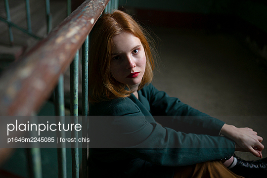 Teenage girl with red hair sitting in the staircase - p1646m2245085 by Slava Chistyakov