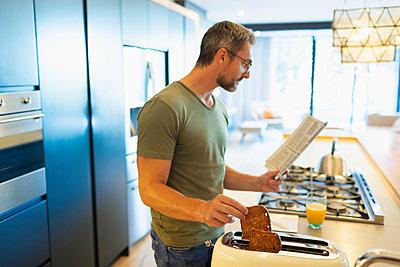 Man reading newspaper and preparing toast in morning kitchen - p1023m2196668 by Paul Bradbury