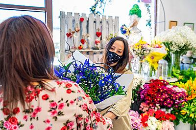enterprising woman handing a bouquet of flowers to her client - p1166m2279528 by Cavan Images
