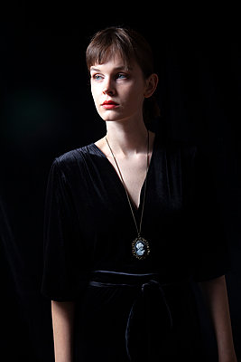 Woman in Black Dress with Cameo Necklace - p1248m2122025 by miguel sobreira