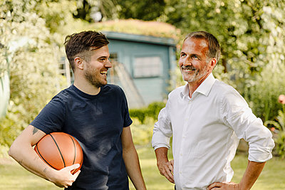 Cheerful son with basketball looking at father while standing in back yard - p300m2274982 by Gustafsson