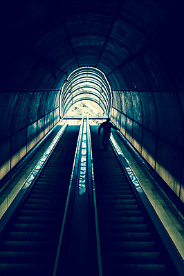 Man on an escalator - p470m1043026 by Ingrid Michel
