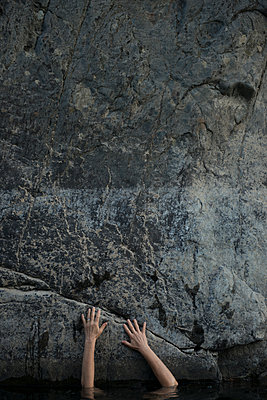 Woman's arms touching rock wall - p920m1573751 by Jude Mooney