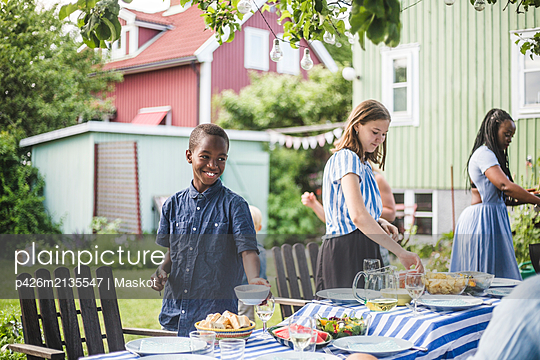 Smiling boy with bowl standing by girl at dining table in backyard party - p426m2135547 by Maskot
