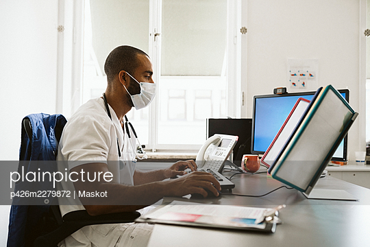 Male doctor using computer while sitting at desk during COVID-19 - p426m2279872 by Maskot