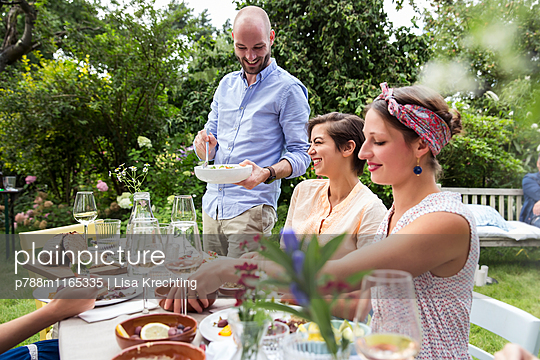 Gemeinsam essen auf einer Gartenparty - p788m1165335 von Lisa Krechting