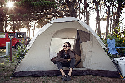Woman wearing sunglasses relaxing in tent - p1166m1210495 by Cavan Images