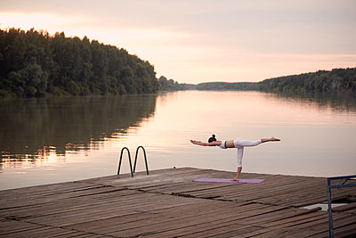 Woman practicing warrior 3 pose on pier by lake against cloudy sky during sunset - p1166m2011228 by Cavan Images