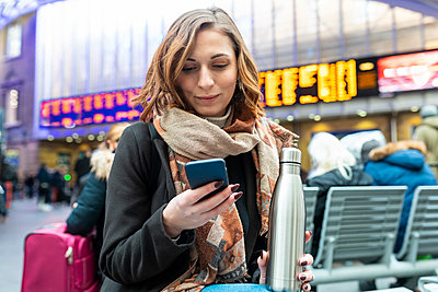 Woman sitting at train station and using mobile phone - p300m2180815 by William Perugini