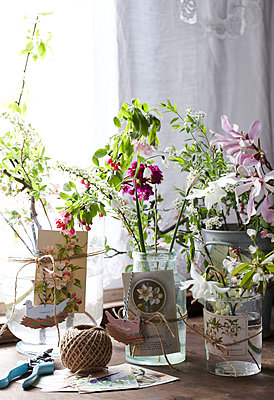 Making floral displays for an Easter table  glass jars and vases with cards tied with string filled with spring flowers beside window - p349m2167885 by Sussie Bell