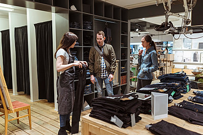 Saleswoman showing jeans to customers at store - p426m2036377 by Kentaroo Tryman