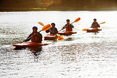 Kayakers rowing together on still lake - p429m665376f by Nick Daly