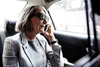 Senior businesswoman sitting in back of taxi, using smartphone - p924m1480591 by SG Hirst