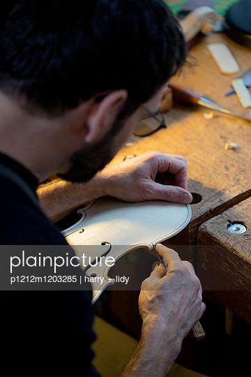 Geigenbauer bearbeitet einen neuen Geigenkorpus - p1212m1203285 von harry + lidy