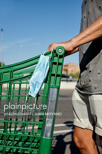 Man in shorts pushing a shopping cart wearing his face mask in his hand - p1423m2204327 by JUAN MOYANO