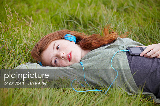 Teenage girl listening to headphones - p42917247f by Janie Airey