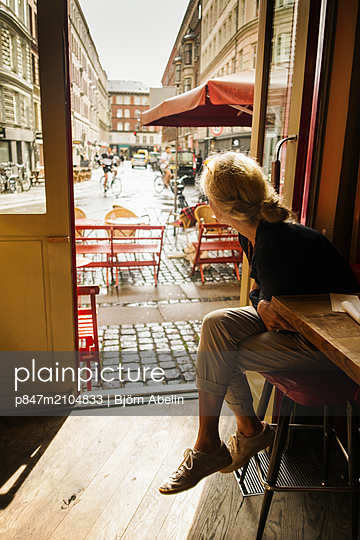 Woman Sitting At Cafe Looking Out Through Open Door, Denmark   - p847m2104833 by Björn Abelin