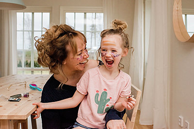 mother and daughter laughing whilst playing with make up at home - p1166m2165842 by Cavan Images