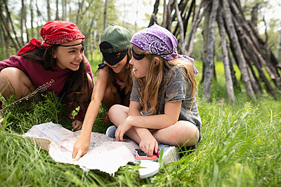 Girl friends in pirate costumes looking at treasure map in woods - p1192m2009443 by Hero Images